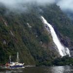 Wasserfall und Boot im Milford Sound