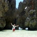 Tourist mit Umhängetasche, Sonnenbrille, T-Shirt und Badeshort am Traumstrand