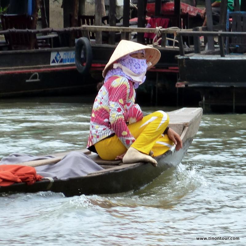 Vor der Sonne geschützt - eine Frau auf ihrem kleinen Boot auf dem Wasser des Mekong