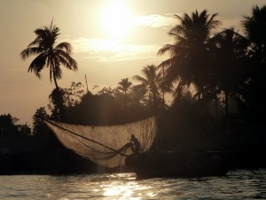 Fischer mit holt beim Sonnenaufgang sein Netz aus dem Mekong