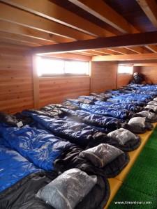 """Wer glaubt in den Hütten der europäischen Alpen ist es eng, der war noch nicht auf einer Hütte hier. Wo in Östtereich, Deutschland und Schweiz vielleicht 50 Leute untergebracht werden, schafft man es hier auf gleichen Platz 200 Leute unterzubringen. Wie? Ganz einfach: der Schlafplatz ist nur ca. 40cm breit, geschlafen wird """"überall"""" und auf den Aufenthaltsraum wird weitestgehend verzichtet."""